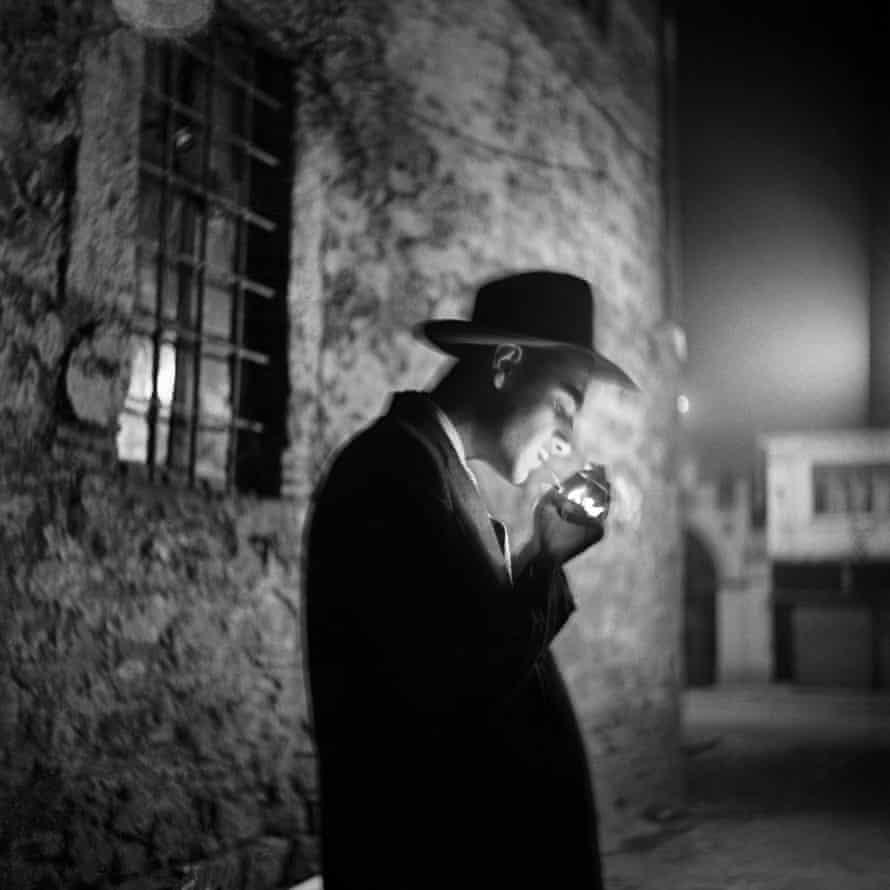 A young man lighting a cigarette in the dark in Beyoğlu, 1954, by Ara Güler.
