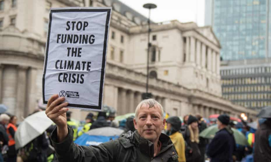 An Extinction Rebellion protester holds a placard saying 'Stop funding the climate crisis' outside the Bank of England on Monday 14 October.