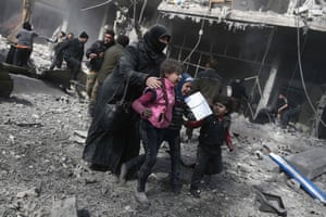A woman and children run for cover amid the rubble of buildings