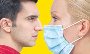Man without mask and woman in mask face off (posed by models)