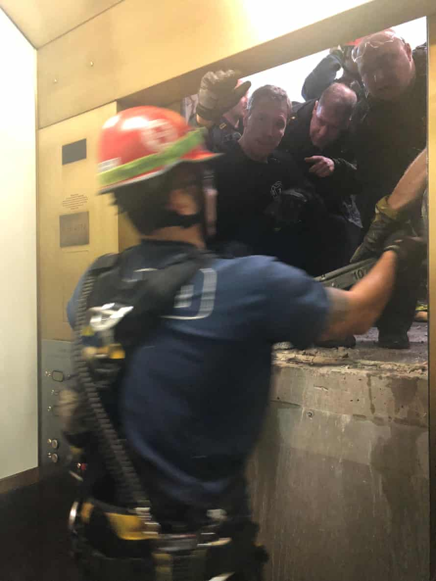 The rescue crew open the door to pull out six people trapped in an elevator of the 875 North Michigan Avenue building in Chicago.