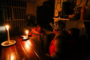 A woman runs her takeaway restaurant by candlelight during a scheduled power outage in the impoverished neighbourhood of Masiphumelele, Cape Town.