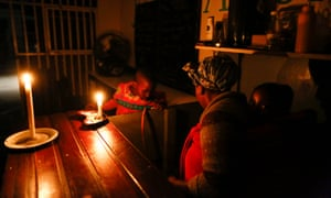 A woman runs her takeaway restaurant by candlelight during a scheduled power outage in the impoverished neighbourhood of Masiphumelele, Cape Town