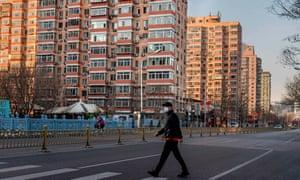 A man wearing a protective mask walks along an empty street in Beijing.