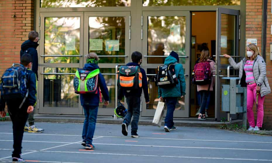 Children respect physical distancing rules at a reopened school in Dortmund