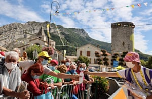 An employee distributes face masks to spectators prior to the 4th stage between Sisteron and Orcieres-Merlette.