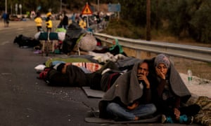 Refugees and migrants camp on a road following a fire at the Moria camp in Greece.