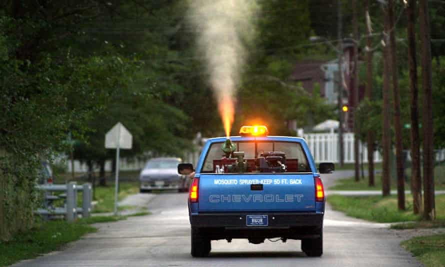 A truck sprays for mosquitoes in residential neighborhoods.