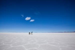 Polish adventurer Mateusz Waligóra walking across the the world's biggest salt flat, the Salar de Uyuni in Bolivia. He is pictured against a deep blue skyline with just a few clouds skimming by.