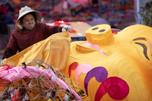 A woman works on a pig-shaped giant lantern at a plaza in Huangshan, Anhui, China