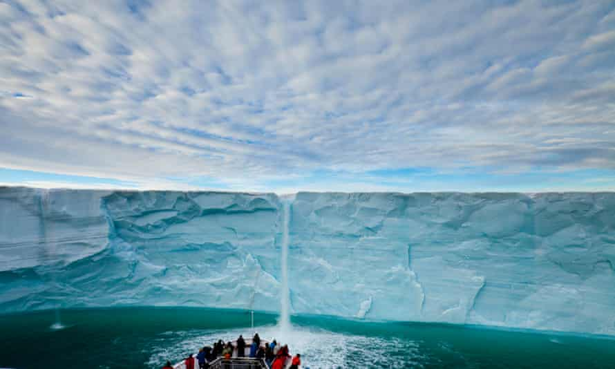 Under a blanket of clouds, tourists watch a meltwater waterfall on an icecap.