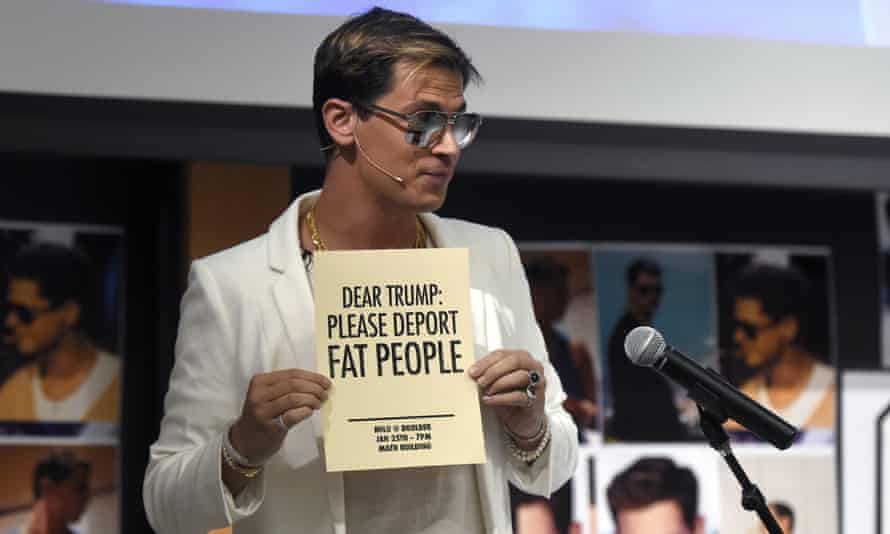 Milo Yiannopoulos holding a 'Deport fat people' sign