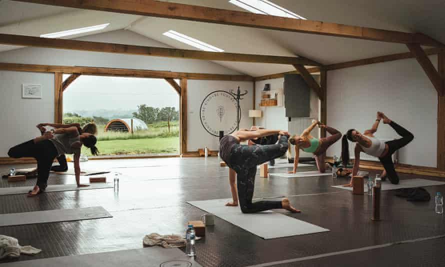 A small group practises yoga on the three-day retreat at Fair Oak Farm, East Sussex, UK