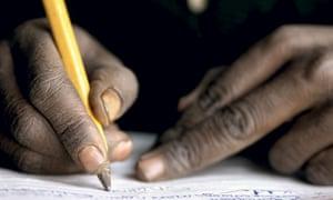 Boy at school, writing, in Tanzania