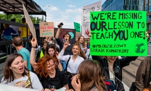 Teenage protesters in Warsaw, Poland, hold up placards calling on politicians to address climate crisis.