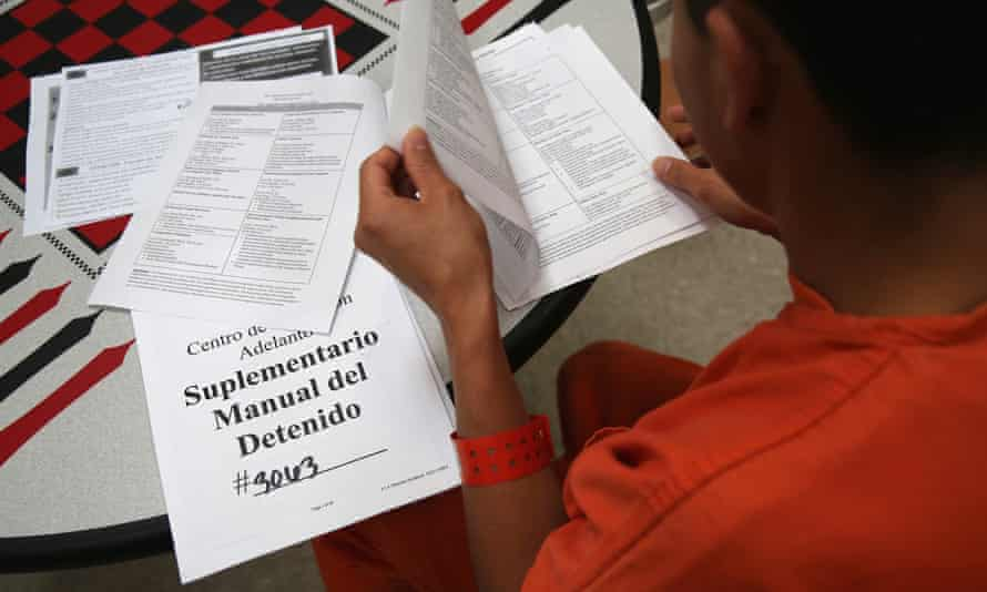 An immigrant detainee reads through paperwork in a general population block at the Adelanto detention facility.