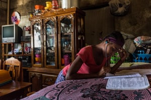 Oieumene, 18, works on her homework in the lounge that is also the main bedroom for the rest of her family