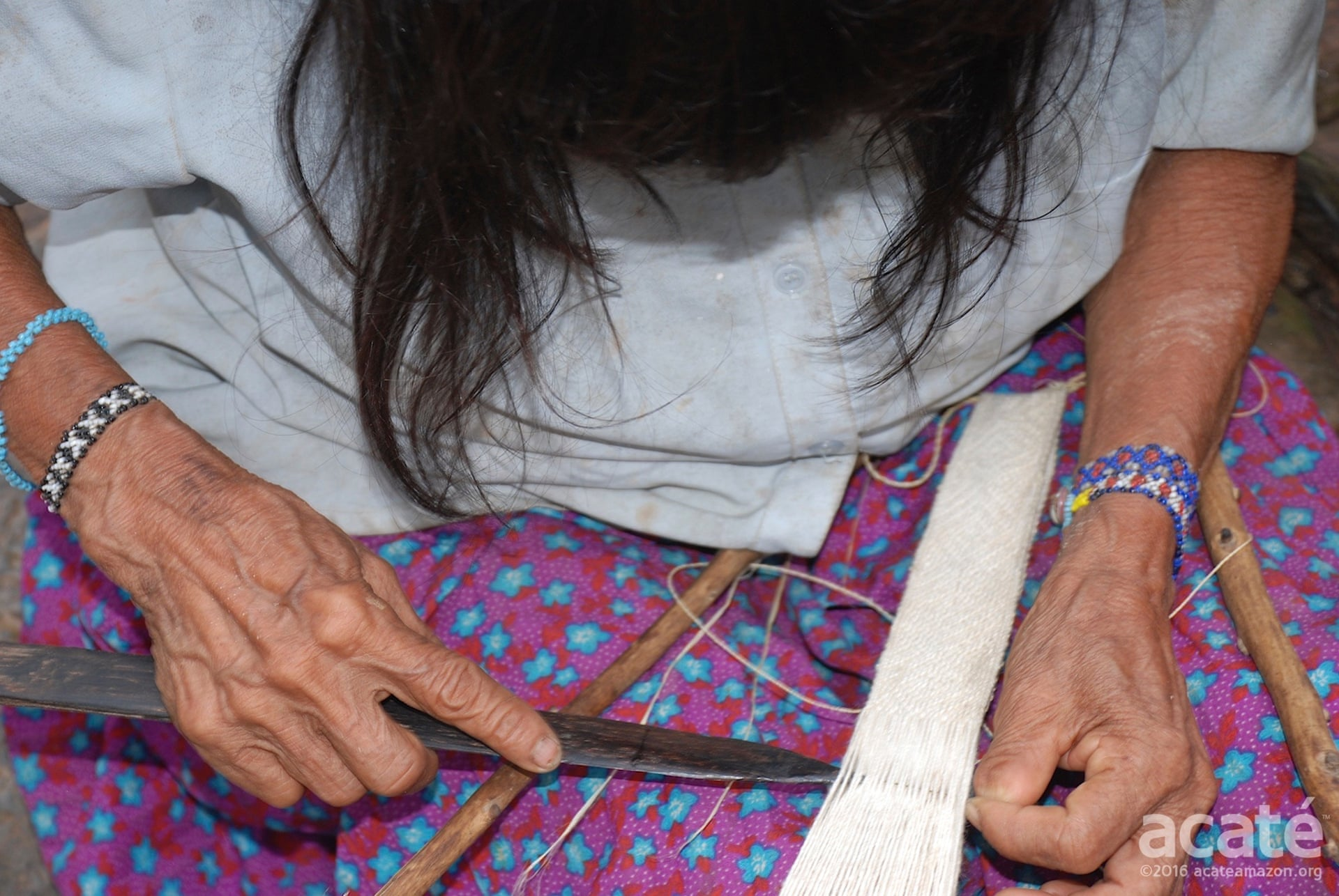 Juama Perez Chispi, Segundo's mother, weaving one of the bracelets. Photograph: Acate Amazon Conservation