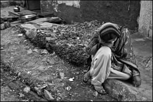 A young woman with developmental issue sits on the pavement outside her home in the Blue Moon neighbourhood of Bhopal, on the edge of the abandoned Union Carbide chemical plant. Her parents survived exposure to the toxic gas cloud released by the explosion at the plant.