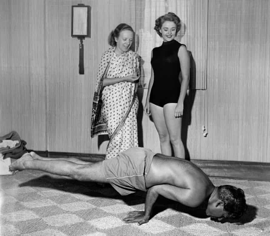Indra Devi (left, standing) instructs a student on a yoga position in her studio in Hollywood, California.