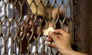 A piece of tortilla is passed through the fence at Friendship Park in 2008, at a time when the fencing was wider.