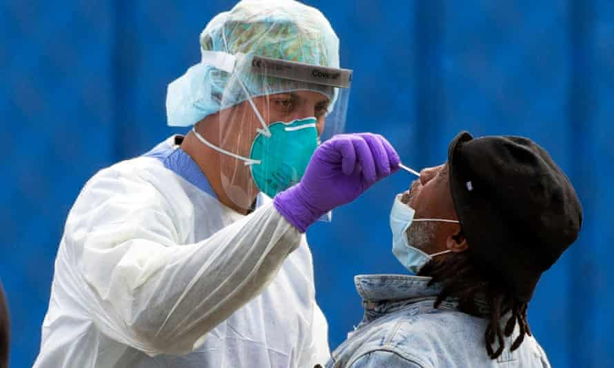 A medical worker performs a Covid-19 test on a patient at a walk-up site in Boston, Massachusetts.