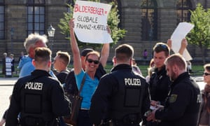 Protestor holding a sign surrounded by police