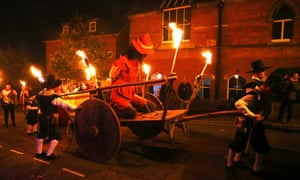 People carrying torches and dragging an effigy during the march through Lewes