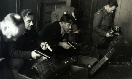 Five men, Polish recruits of the Cichociemni, in uniforms holding handguns