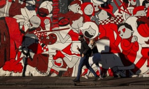 People wearing masks walks past a wall mural on 6 September 2020 in Melbourne, Australia.