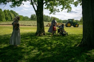 A family watches the tractor work the fields on the farm in the Foxhill community, Upstate NY