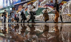 People wearing face masks walk through Shibuya area in Tokyo, Japan. Japan is banning all spectators for the Paralympics amid a surge in Covid cases.