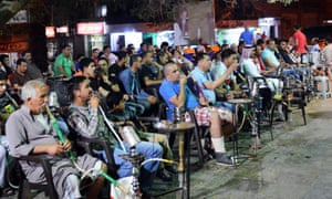 Jordanians smokign while watching a football match.