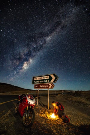 A motorcyclist lights a fire under the stars and and sign pointing to Tumbarumba