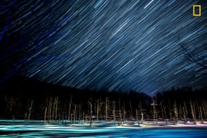 The man-made water feature in Biei, Hokkaido, Japan. The long exposure time shows stars streaking across the sky above barren trees and a blue pond.