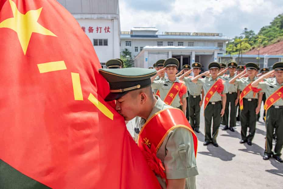 A demobilized soldier kisses the Chinese People's Liberation Army (PLA) flag during a farewell ceremony on August 30, 2021 in Yulin, Guangxi Zhuang Autonomous Region of China.