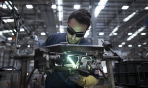 An employee welds a tension tube for a Brompton folding bicycle