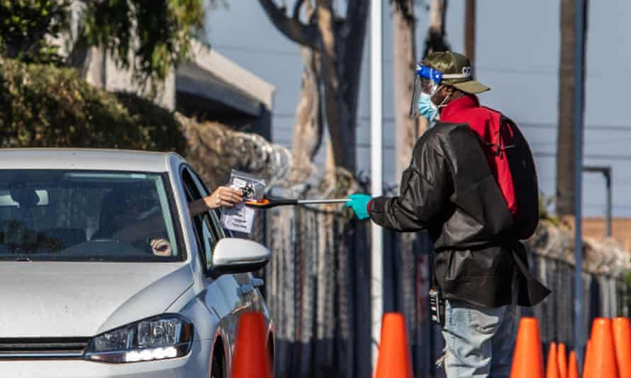 A testing center worker uses a stick to collect tests at a drive through site in Los Angeles.