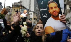 The sister of Elias Wardini, a Lebanese man killed in the nightclub attack, mourns as she holds her brother's portrait during his funeral procession