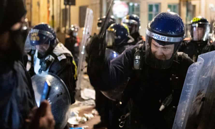 A police officer swings a baton at a protester during a demonstration in Bristol last week.