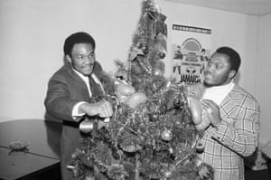Heavyweight boxing champion Joe Frazier, right, and challenger George Foreman joke around the Christmas tree during a press conference to promote their January 1973 title fight in Kingston, Jamaica