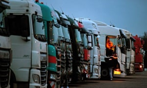 Drivers of freight lorries and heavy goods vehicles are illuminated by the lights inside their cabs as they are parked at a truck stop off the M20 leading to Dover, near Folkestone in Kent, south east England on 22 December.