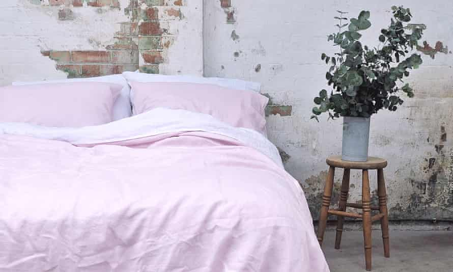 A double bed made with pink and white bedding in a rustic room