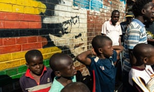 Children stand besides a mural of Robert Mugabe in the Mbare district of Harare