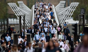 Commuters cross a bridge on their way to work