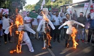 Activists in Guwahati, in Assam, burn effigies of Narendra Modi, centre, and other politicians