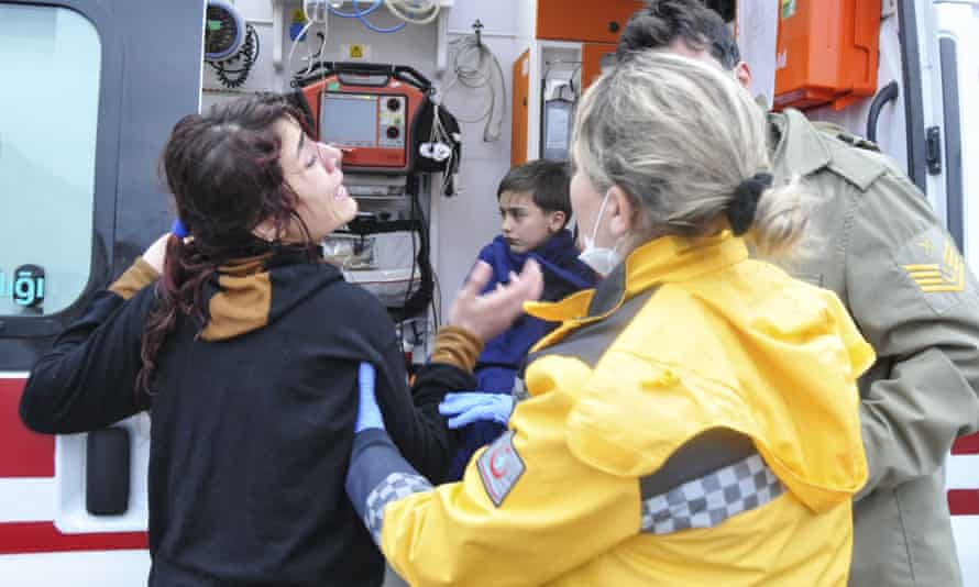 A woman and boy are attended to by a Turkish medical team after a boat sank in the Aegean.