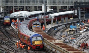 Workers examine a train that was partially derailed at Waterloo train station in London.