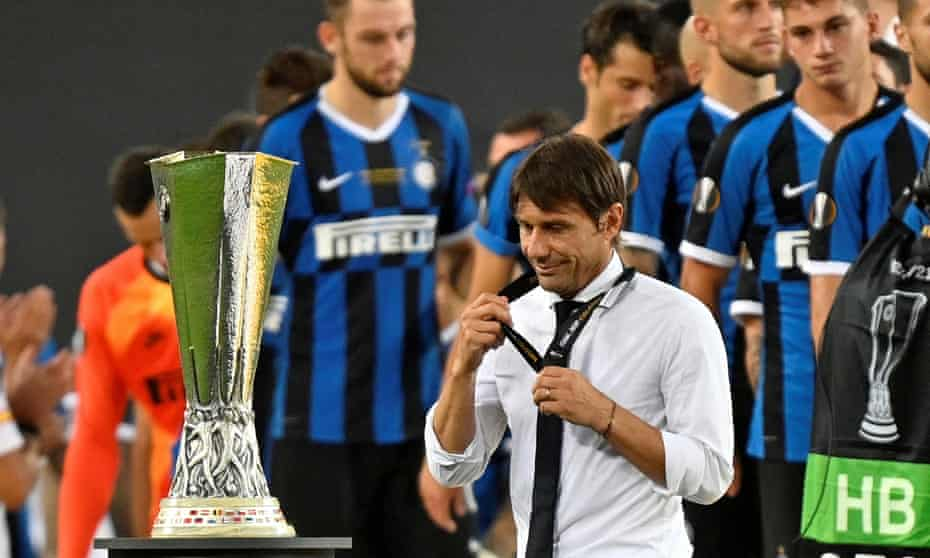 Antonio Conte removes his runners-up medal as he walks past the trophy.