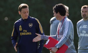 Unai Emery and Mesut Özil share a handshake during Arsenal training but the German will not travel to his homeland for the Europa Cup tie against Eintracht Frankfurt.
